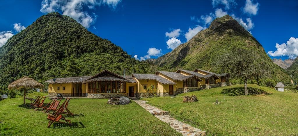 two lush green hills behind yellow salkantay hiking tour lodge
