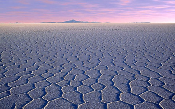 beautiful view of the cracked earth slat flats with purplish pink sunset and mountain in the distance