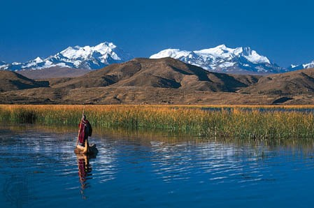 local floating on a reed boat on lake titicaca with snow covered mountain peaks in the distance