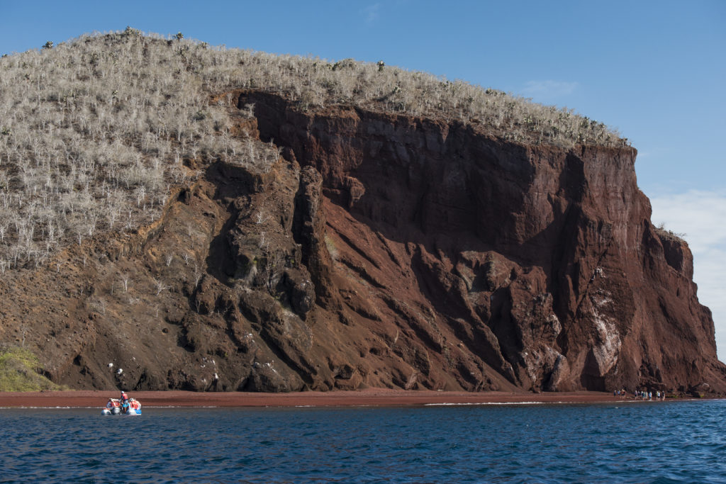 dingy beached near a rocky cliff on day excursion on galapagos island cruise tour